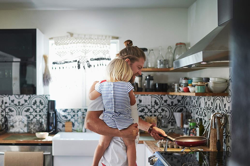 Man holding child while cooking