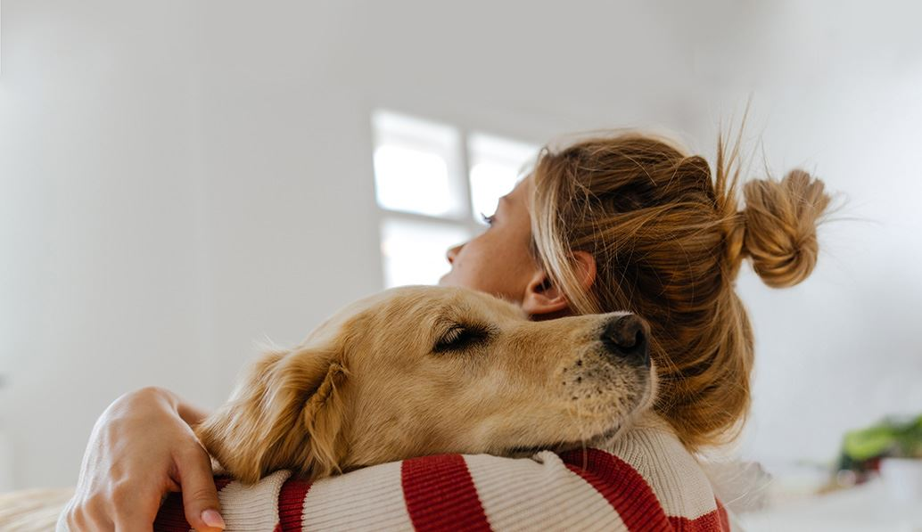 Young woman cuddling pet dog