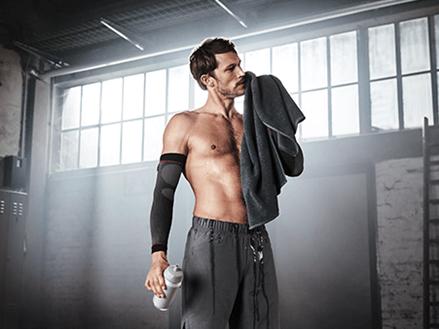 Mann trägt Arm-Kompression zur Leistungssteigerung