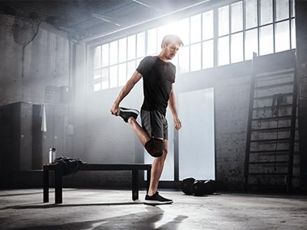 Mann im Fitnessraum mit anatomisch stützender Kniebandage