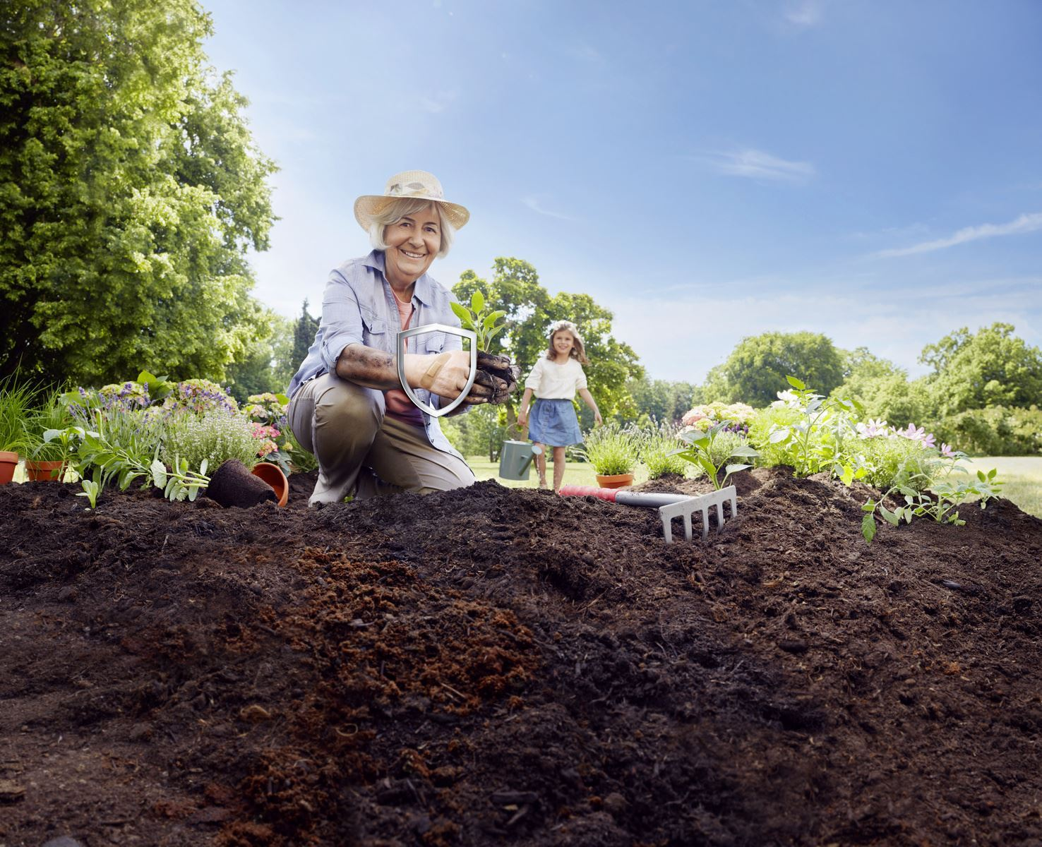 A woman kneels while gardening. She is holding soil but a plaster on her hand is clean.